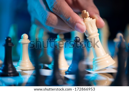 Male hand moving the queen - stock photo