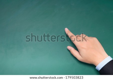 male hand of businessman in a suit pointing to something on the green chalkboard - stock photo