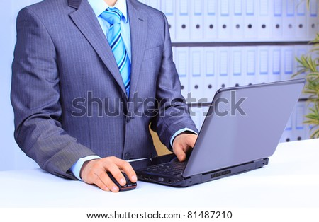 Male hand on mouse while working on laptop - stock photo