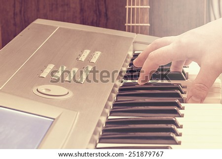 Male hand on the digital midi keyboard and guitar in the studio. - stock photo