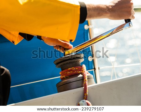 Male hand on winch capstan with rope on sailing boat. Yachting yacht in blue baltic sea sunny day summer vacation. Tourism luxury lifestyle. - stock photo