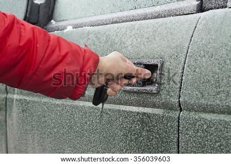 Male hand opening frozen car door with keys, selective focus outdoor shot - stock photo