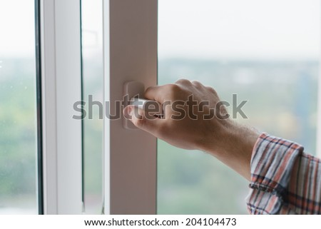 Male hand opens a window - stock photo