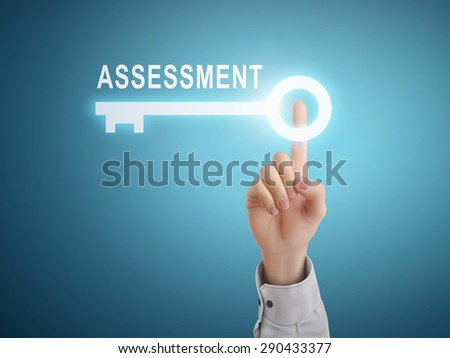 male hand pressing assessment key button over blue abstract background - stock photo