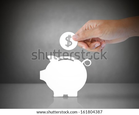 Male hand putting paper coin into a paper piggy bank - stock photo