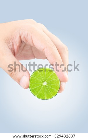Male hand squeezing lime with clipping path - stock photo