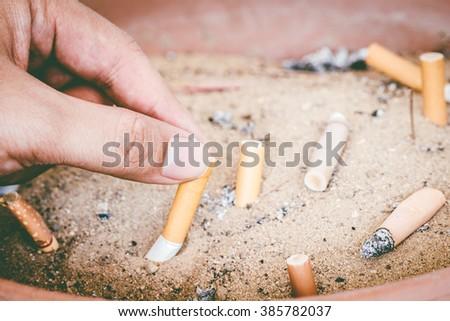 Male hand Stubbing Out Cigarette in sand ashtray bin - stock photo