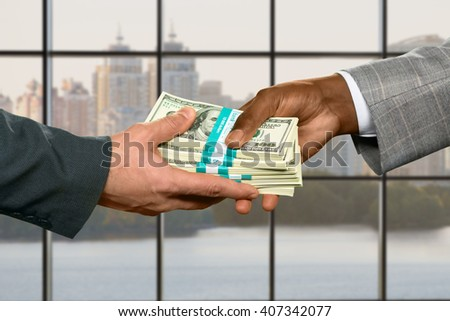 Male hand taking big money. Money transfer on city background. Strong leader's inheritance. Purchasing real estate on credit. - stock photo