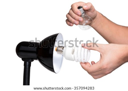 Male hand to get out of luminaire incandescent bulb and the twists in its place energy-saving lamp isolated on white background - stock photo