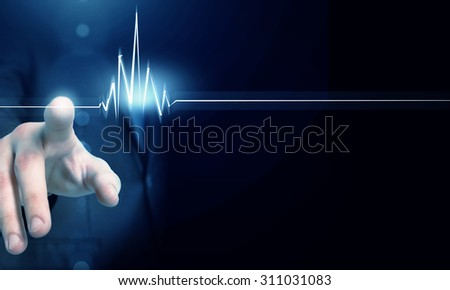 Male hand touch heart pulse on futuristic interface - stock photo