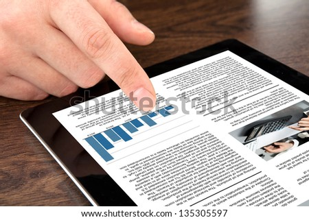 male hand touching computer tablet with business news on screen - stock photo