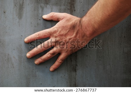Male hand touching the gray grunge surface of a stained concrete wall, close-up - stock photo