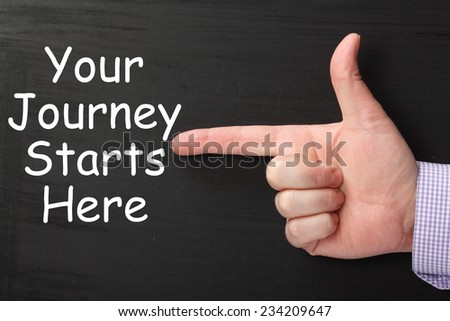 Male hand wearing a business shirt pointing a finger at the phrase Your Journey Starts Here written on a blackboard - stock photo