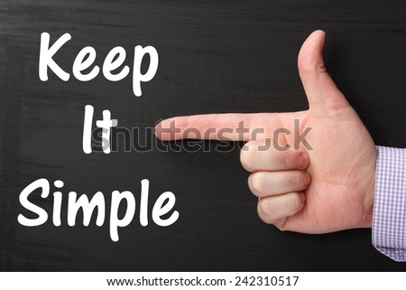 Male hand wearing a business shirt pointing an index finger at the phrase Keep It Simple written on a blackboard - stock photo