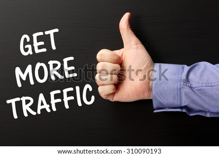 Male hand wearing  business shirt giving the thumbs up sign for the phrase Get More Traffic as a reminder that online retailers need marketing to attract customers - stock photo