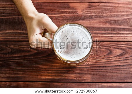 Male hand with a glass of beer, pub interior. - stock photo