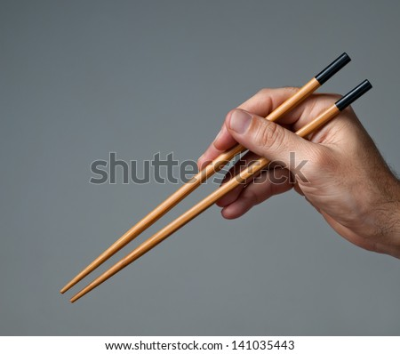 Male hand with chinese chopsticks. - stock photo