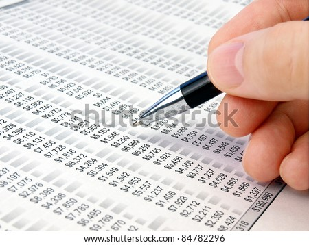 Male hand with pen analyzing  financial data. - stock photo