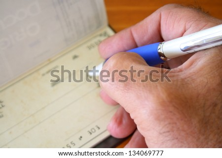 Male hand with pen filling a bank check - stock photo