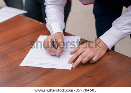 Male hand with pen filling in the personal information form, questionnaire,  document. Hand with pen over blank - stock photo