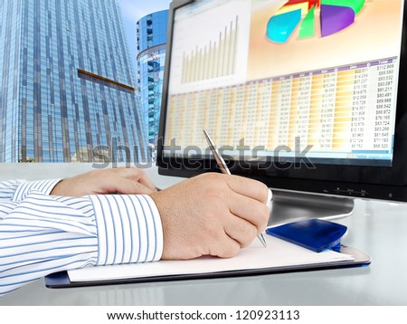 Male Hand with Pen in Front of Computer Screen with Financial Data and Charts - stock photo
