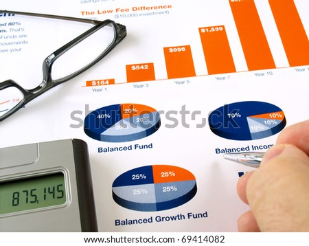 Male hand with pen on the investment chart with calculator and glasses - stock photo