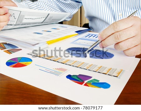 Male hand with pen on the investment charts. - stock photo