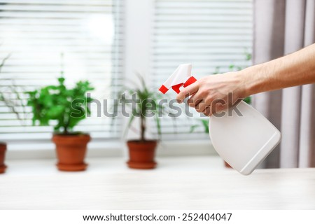 Male hand with sprayer wash windowsill on window background - stock photo