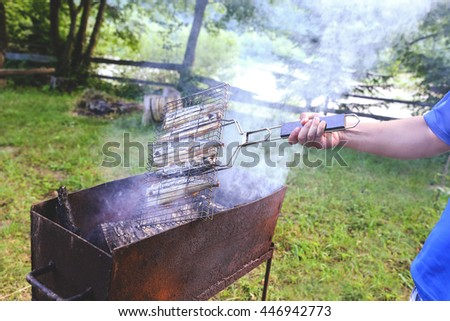 Male hand with tasty mackerel, cooked on the grill in the open air. Five fishes on the grill in the smoke, tasty and fresh food, picnic, party, outdoor recreation. Grilled fish dish. - stock photo