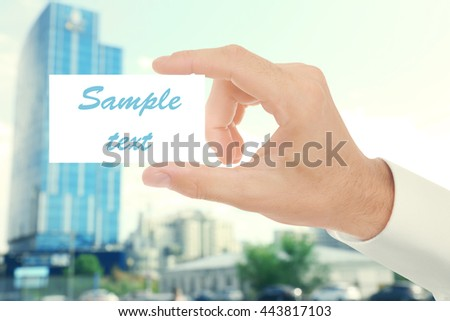 Male hand with white blank card on blur abstract city background - stock photo
