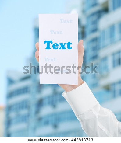 Male hand with white paper on multi-storey building blurred background - stock photo
