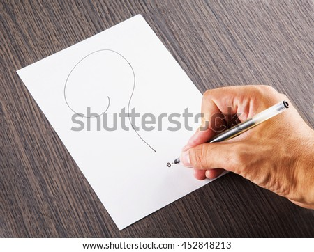 Male hand writing a question mark, horizontal image - stock photo