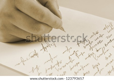 Male hand writing on a paper - stock photo