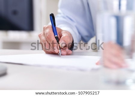 Male hand writing on a paper, signing a contract - stock photo