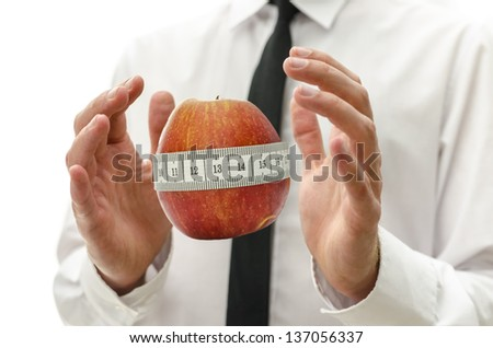 Male hands around apple wrapped with measuring tape. Concept of healthy and responsible dieting. - stock photo