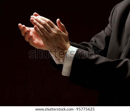 Male hands clapping on black, side-view - stock photo