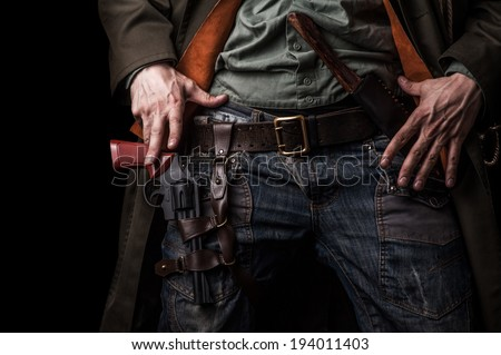 Male hands cowboy and a revolver on his belt on black background - stock photo