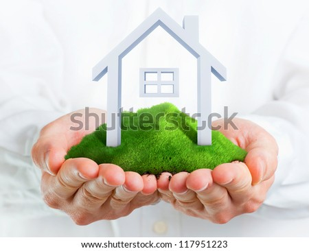 Male hands holding a green hill with a small house - stock photo