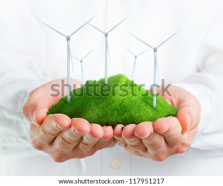 Male hands holding a green hill with wind turbines - stock photo