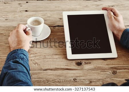 male hands holding a tablet computer with blank screen closeup. Tablet computer with a cup of coffee on the wooden desk. Top view. Copy space. Free space for text. Vintage photo toning - stock photo