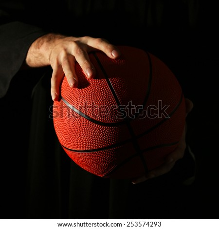 Male hands holding basketball ball on dark background - stock photo