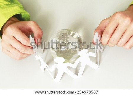 Male hands holding paper people around a glass globe - stock photo