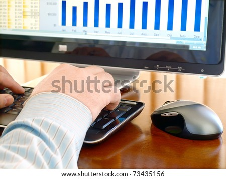 Male hands on the keyboard in front of computer screen with charts - stock photo