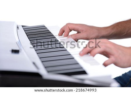 Male hands playing digital piano. Isolated over white background. - stock photo