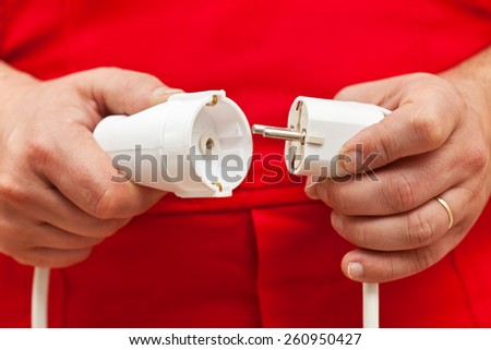 Male hands plugging or unplugging electrical jack and receptacle - stock photo