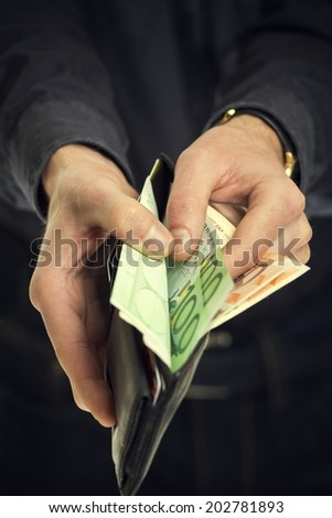 Male hands pulling out 100 hundred euro banknotes from wallet. Shallow depth of field. - stock photo