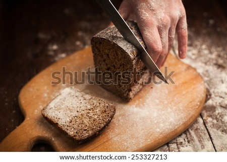 Male hands slicing fresh bread on wood table - stock photo