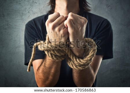 Male hands tied with a rope. Captivity concept. - stock photo