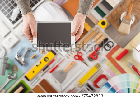 Male hands using a digital tablet, construction and home decoration tools on background, top view, DIY and home improvement mobile app concept - stock photo