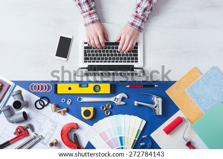 Male hands using a laptop next to plumbing work tools, tiles and swatches, online booking and home plumber service - stock photo